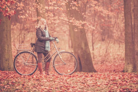 active: Happy active woman riding bike bicycle in fall autumn park. Glad young girl in jacket and scarf relaxing. Healthy lifestyle and recreation leisure activity.