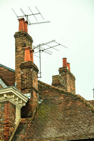 rooftiles: Roof tops and brick chimneys on house in typical english town