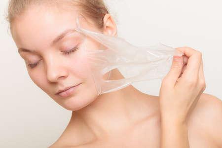 tratamientos corporales: Belleza cosméticos cuidado de la piel y el concepto de salud. Primer rostro de mujer joven, muchacha que quita facial mascarilla exfoliante en gris. Descamación Foto de archivo