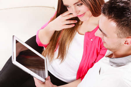 websurfing: modern technologies leisure and relationships concept. Young couple using pc computer tablet sitting on couch at home websurfing on internet, high angle view Stock Photo