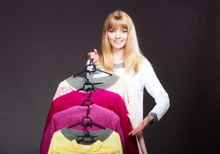 invitando: Al por menor y venta. Muchacha rubia mujer mostrando la ropa de moda. Cliente Cliente sosteniendo perchas con la toma de la ropa acogedor gesto de la mano