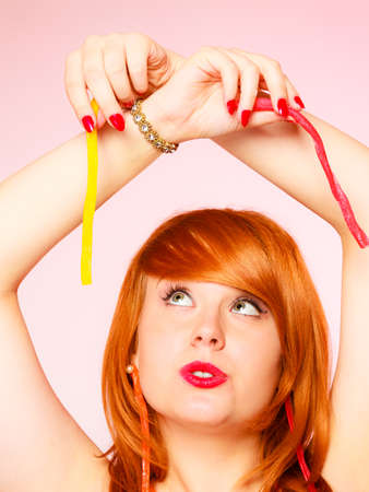 red haired woman: Dependence on sweets. Young red haired woman with candy on pink background in studio.