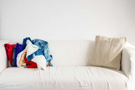 messy clothes: Messy colorful clothing on white sofa, heap of clothes indoor Stock Photo
