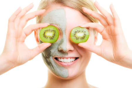 wellfare: Skin care. Woman in clay mud mask on face covering eyes with slices of kiwi isolated. Girl taking care of dry complexion. Stock Photo
