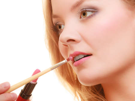 Cosmetic beauty procedures and makeover concept. Closeup part of woman face pink lips. Make-up artist applying lipstick with accessories tools.