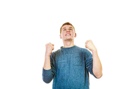 lad: Success positive emotions. Happy young man successful lad with arms up looking upwards clenching fist isolated on white