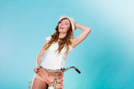 Active smiling woman riding bike bicycle. Young girl in hat, white shirt and shorts. Healthy lifestyle and recreation leisure activity. Studio shot.