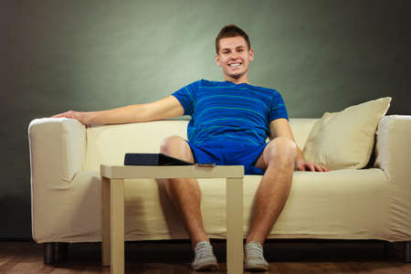 sleeping tablets: Young man relaxing on couch, tablet and mobile phone laying on table Stock Photo