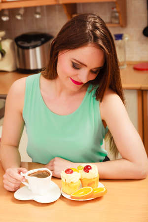 glutton: Woman drinking coffee and having breakfast. Glutton girl sitting in kitchen with hot beverage, delicious gourmet sweet cream cake cupcake and orange. Appetite and gluttony concept.