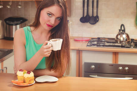 glutton: Woman drinking coffee and eating delicious gourmet sweet cream cake. Glutton girl sitting in kitchen with hot beverage and cupcake. Appetite and gluttony concept.