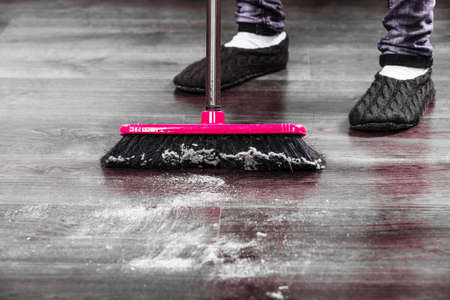 charwoman: Cleanup housework concept. Closeup broom and female foots. Cleaning woman sweeping wooden floor. Stock Photo