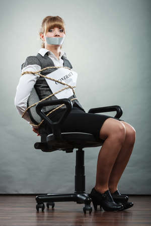 bound: Afraid businesswoman bound by contract terms and conditions with mouth taped shut. Scared woman tied to chair become slave. Business and law concept. Stock Photo