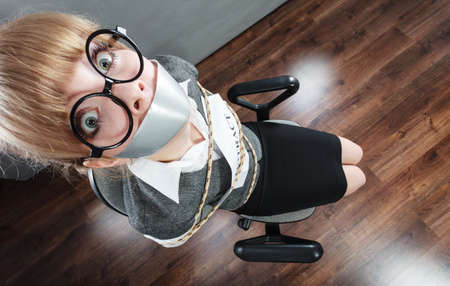 Afraid businesswoman bound by contract terms and conditions with mouth taped shut. Scared woman tied to chair become slave. Business and law concept. Imagens