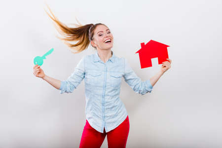 rent: Happy young woman girl holding red paper house and key dreaming about new home house. Housing and real estate concept. Stock Photo