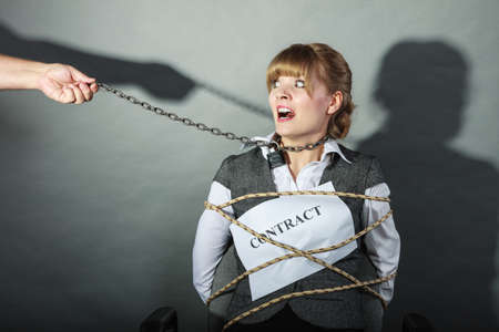 slave girl: Scared businesswoman bound by contract terms and conditions.  Afraid and helpless woman tied to chair become slave. Human hand hold chain and has power over girl. Business and law concept. Stock Photo