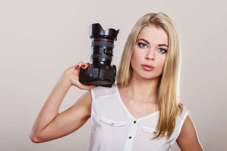 photojournalism: Photographer girl shooting images. Lovely blonde woman with professional camera on gray background