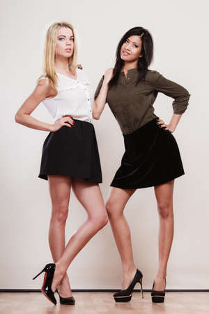 skirts: Two young women of caucasian and african trends in short black skirts posing in full length studio portrait on gray Stock Photo