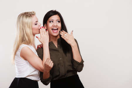 secret: Relationship gossip. Two women multiethnic whispering secret surprised face expression, studio shot Stock Photo