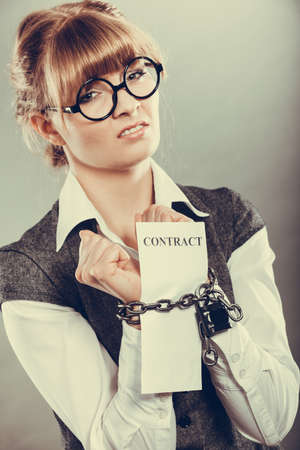 slave labor: Business concept. Serious businesswoman with chained hands holding contract Stock Photo