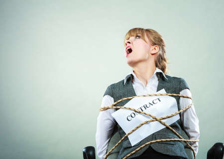 bound woman: Afraid businesswoman bound by contract terms and conditions. Screaming scared woman tied to chair become slave. Business and law concept.