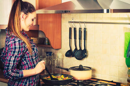 Woman in kitchen cooking stir fry frozen vegetables. Girl frying making delicious risotto. Dinner food meal.     Banco de Imagens