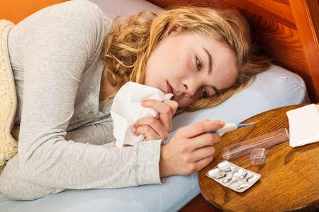 termómetro: Mujer enferma que pone en la cama bajo la manta de lana que sostiene el termómetro y el tejido. Muchacha enferma llamó gripe frío. Las píldoras y tabletas en la mesa. Foto de archivo