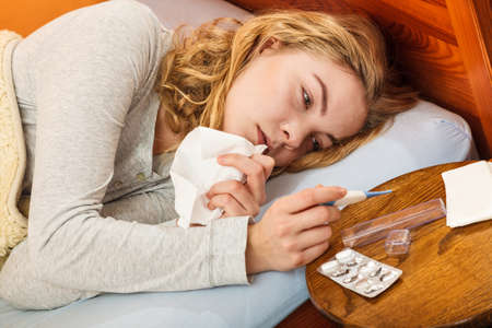 thermometer: Sick woman laying in bed under wool blanket holding thermometer and tissue. Ill girl caught cold flu. Pills and tablets on table.