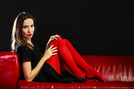 Elegance and fashion outfit. Fashionable woman legs in red vivid color tights posing on couch black background Stock Photo