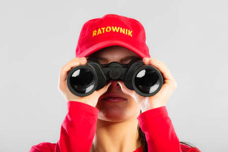 observant: Accident prevention and water rescue. Closeup girl in red lifeguard outfit cap with polish word ratownik on duty looking through binocular on gray Stock Photo