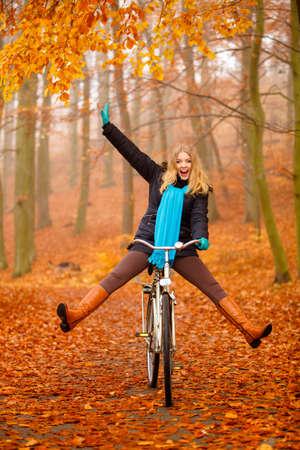 Automne concept de style de vie actif. Bonne fou femme fille vive châle de couleur relaxante dans le parc de l'automne équitation vélo avec ses jambes en l'air amusant