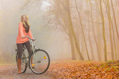 Active woman girl relaxing riding bike bicycle in fall autumn park. Healthy lifestyle.