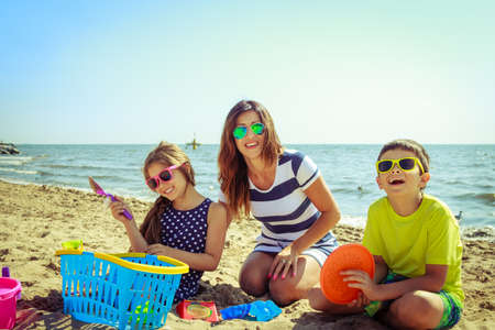 relax beach: Happy family mother, daughter and son having fun on beach sand. Parent mom and children kids with toys at sea. Summer vacation holidays relax and happiness.