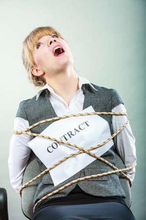 scared woman: Afraid businesswoman bound by contract terms and conditions. Screaming scared woman tied to chair become slave. Business and law concept.