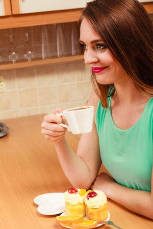 gula: Mujer de tomar caf� y desayunar. Glot�n chica sentada en la cocina con la bebida caliente, delicioso gourmet magdalena dulce pastel de crema y naranja. El apetito y el concepto de la gula. Foto de archivo