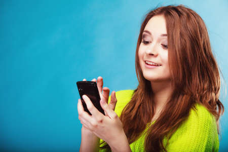 Technology and communication. Happy woman teenage girl texting on mobile phone, using smartphone reading sms message on blue