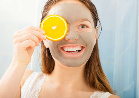 lemon slices: Smiling woman with orange slice and mud mask on face in bathroom Stock Photo