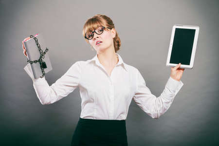 chained: Businesswoman holding document and tablet. Choice between digital and physical data storage. Woman with padlock chained file and pc computer.
