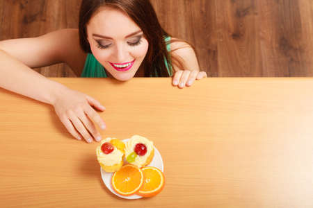 sneaking: Woman hidden behind table sneaking and looking at delicious cake with sweet cream and fruits on top. Appetite and gluttony concept. Stock Photo