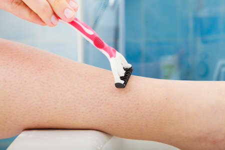 depilate: Hygiene skin body care concept. Hair removal. Closeup woman shaving legs with razor blade in bathroom