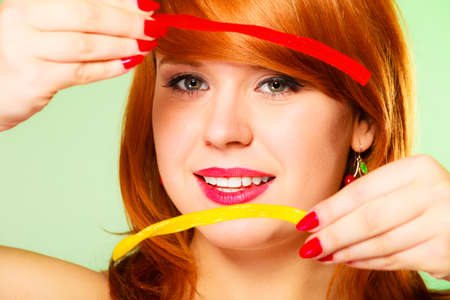 red haired woman: Dependence on sweets. Young red haired woman with candy on green  Stock Photo