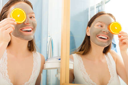 clay: Beauty skin care cosmetics and health concept. Young woman with facial clay mask holding orange fruit slice covering eyes in bathroom Stock Photo