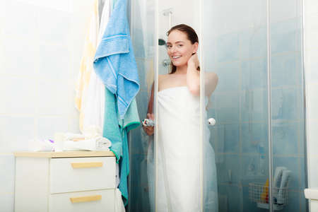 shower: Girl showering in shower cabin cubicle enclosure. Young woman with white towel taking care of hygiene in bathroom. Stock Photo