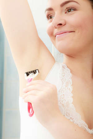 underarm: Woman shaving armpit armhole with razor shaver. Young girl removing underarm hair. Hygiene. Stock Photo