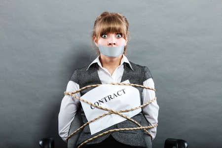 stressed business woman: Afraid businesswoman bound by contract terms and conditions with mouth taped shut. Scared woman tied to chair become slave. Business and law concept. Stock Photo