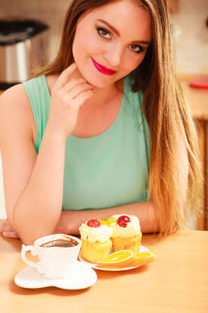 gluttony: Woman with cup of coffee and delicious gourmet sweet cream cake cupcake and orange. Glutton girl sitting in kitchen with hot beverage having breakfast. Appetite and gluttony concept.