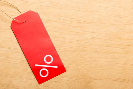 blank tag: Shopping and sale concept. Red price label with percent sign on wooden surface background. Copyspace