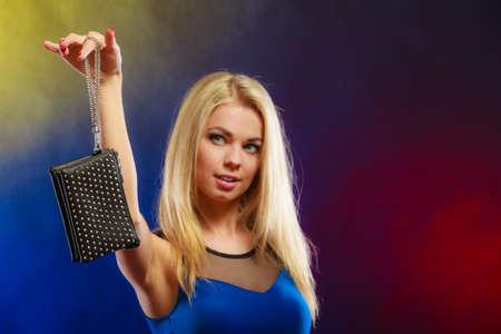 woman fashionable: Fashion elegant evening outfit. Stylish woman fashionable blonde girl holding black rivet leather handbag bag in night club dancing.