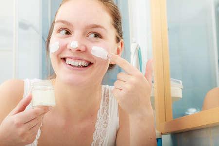 piel: Mujer joven feliz aplicar crema para la piel limpieza hidratante en la cara. Muchacha que toma el cuidado de la crema hidratante seca estratificaci�n tez. Protecci�n De La Piel.