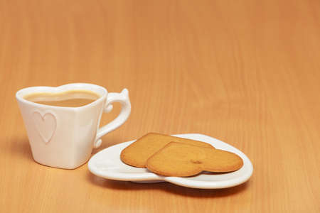 stimulate: Heart shape gingerbread cookies and hot beverage tea or coffee on table.