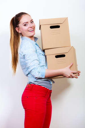 arranging: Woman moving in carrying cartons boxes. Young girl arranging interior and unpacking at new apartment house home.